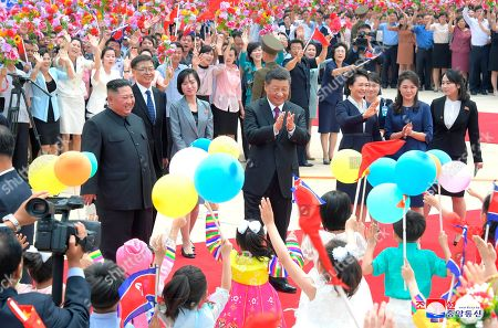 "Provided by the North Korean government, Chinese President Xi Jinping, center, is welcomed by North Koran children at Pyongyang International Airport in Pyongyang, North Korea. North Korean leader Kim Jong Un, left, his wife Ri Sol Ju, second right, and Xi's wife Peng Liyuan, fourth right, also attended a welcoming ceremony. The content of this image is as provided and cannot be independently verified. Korean language watermark on image as provided by source reads: ""KCNA"" which is the abbreviation for Korean Central News Agency"