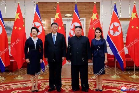 "Provided by the North Korean government, North Korean leader Kim Jong Un, center right, his wife Ri Sol Ju, right, Chinese President Xi Jinping, center left, and his wife Peng Liyuan pose for a photo at Kumsusan guest house in Pyongyang, North Korea. The content of this image is as provided and cannot be independently verified. Korean language watermark on image as provided by source reads: ""KCNA"" which is the abbreviation for Korean Central News Agency"
