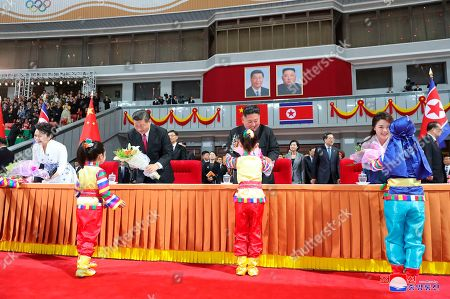 "Provided by the North Korean government, North Korean leader Kim Jong Un, center right, and his wife Ri Sol Ju, right, Chinese President Xi Jinping, center left, and his wife Peng Liyuan receive flowers from children during a mass gymnastic performance at the May Day Stadium in Pyongyang, North Korea. The content of this image is as provided and cannot be independently verified. Korean language watermark on image as provided by source reads: ""KCNA"" which is the abbreviation for Korean Central News Agency"