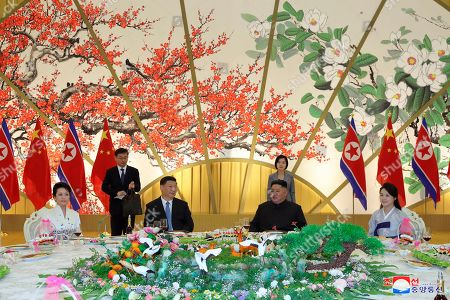 "Provided by the North Korean government, North Korean leader Kim Jong Un, center right, his wife Ri Sol Ju, right, Chinese President Xi Jinping, center left, and his wife Peng Liyuan attend at a banquet in Pyongyang, North Korea. The content of this image is as provided and cannot be independently verified. Korean language watermark on image as provided by source reads: ""KCNA"" which is the abbreviation for Korean Central News Agency"