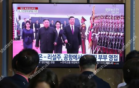 "People watch a TV showing North Korean leader Kim Jong Un, second from left, welcoming Chinese President Xi Jinping at Pyongyang airport, at the Seoul Railway Station in Seoul, South Korea, . North Korea's state media says leader Kim Jong Un and Chinese President Xi Jinping held broad discussions over the political situation surrounding the Korean Peninsula and called for stronger bilateral ties in the face of ""serious and complicated changes"" in the region. The signs read: "" Kim Jong Un and his wife Ri Sol Ju welcome Xi Jinping and his wife"
