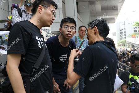 Pro-democracy activist Joshua Wong (C) speaks to legislators Au Nok-hin (L) and Eddie Chu (R) as protesters gather outside the Wanchai Police headquarters in Hong Kong, China, 21 June 2019. Hong Kong is braced for new demonstrations as the government did not respond to a list of protester demands, such as a complete withdrawal of an extradition bill and investigation into police brutality.