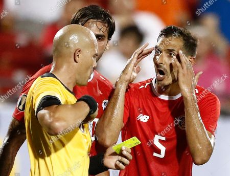 Celso Borges (R) and Bryan Ruiz (C) of Costa Rica argue a yellow card with an official in the second half of the CONCACAF Gold Cup group stage soccer match between Costa Rica and Bermuda at the Toyota Stadium, in Frisco, Texas, USA, 20 June 2019.