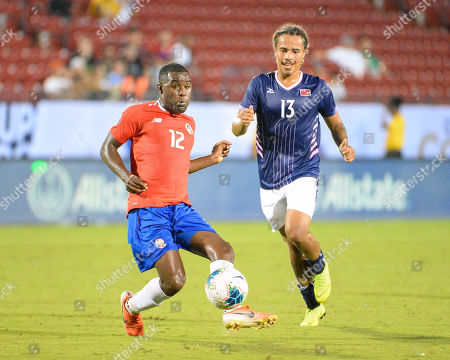 Costa Rica forward, Joel Campbell (12), makes the pass as Bermuda midfielder, Osagi Bascome (13), follows closely behind, during CONCACAF Gold Cup match between Costa Rica and Bermuda, at Toyota Stadium in Frisco, TX. Costa Rica defeated Bermuda, 2-1. Mandatory Credit: Kevin Langley/Sports South Media/CSM