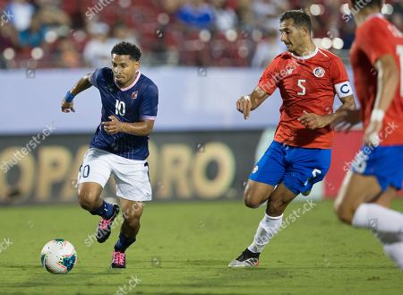 Bermuda midfielder Zeiko Lewis (10) dribbles the ball as he is chased by Costa Rica midfielder Celso Borges (5) during the first half of a CONCACAF Gold Cup soccer match in Frisco, Texas