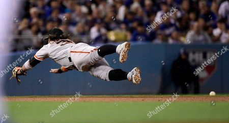 San Francisco Giants shortstop Brandon Crawford dives for but can't stop a ingle by Los Angeles Dodgers' David Freese during the fourth inning of a baseball game, in Los Angeles