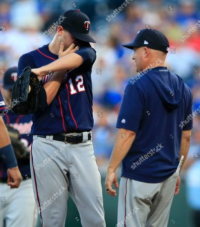 Minnesota Twins starting pitcher Jake Odorizzi (12) talks with pitching coach Wes Johnson, right, during the first inning of a baseball game against the Kansas City Royals at Kauffman Stadium in Kansas City, Mo