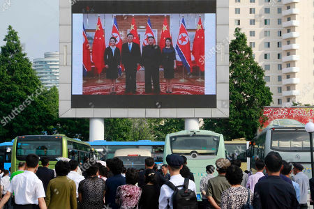 Stock Image of People watch a large screen showing an image of Chinese President Xi Jinping, second from left, posing with his wife Peng Liyuan, left, North Korean leader Kim Jong Un and his wife Ri Sol Ju, at Pyongyang Railway Station in Pyongyang, North Korea, . Xi offered encouragement for North Korea's focus on economic development in a speech in Pyongyang, turning to a topic Beijing has long pressed with its communist neighbor amid wider concerns over the North's nuclear weapons program