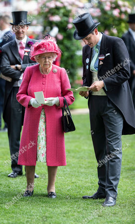 Queen Elizabeth II chats with Jake Warren in the parade ring before watching her horse Magnetic Charm in the Sandringham Stakes race.