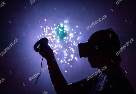 Stock Photo of A woman tests the interactive installation 'Spheres - Songs of the Spacetime' (Virtual Reality, 2018) by US artist Eliza McNitt during the Silbersalz festival in Halle (Saale), Germany, . It is the first international science film festival of its kind and provide the general public with access to scientific topics and to allow them to ask questions, thereby promoting a lively and active engagement with science in general. The festival started on June 20, 2019 and lasts until July 23, 2019