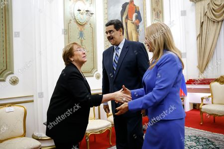 U.N. High Commissioner for Human Rights Michelle Bachelet, left, is greeted by Venezuela's first lady Cilia Flores, right and President Nicolas Maduro, at Miraflores Presidential Palace, in Caracas, Venezuela, . The United Nations' top human rights official is visiting Venezuela amid heightened international pressure on President Maduro