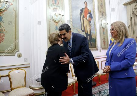 U.N. High Commissioner for Human Rights Michelle Bachelet, left, is greeted by Venezuela's President Nicolas Maduro, as first lady Cilia Flores looks, at Miraflores Presidential Palace, in Caracas, Venezuela, . The United Nations' top human rights official is visiting Venezuela amid heightened international pressure on President Maduro