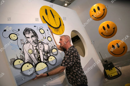 Fatboy Slim, aka Fat Boy Slim, hangs a painting by The London Police titled Having a Ball, tribute to Harvey Ball, at the Underdogs Gallery in Lisbon,. Smile High Club, an exhibition of art works that incorporate the smiley face and curated by Cook, opens Friday at the gallery