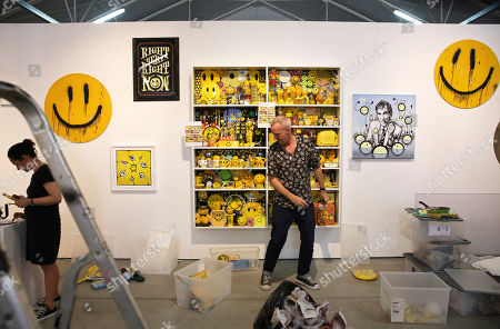 Fatboy Slim, aka Fat Boy Slim, assembles his collection of objects featuring the smiley face symbol on shelves, at the Underdogs Gallery in Lisbon,. Smile High Club, an exhibition of art works that incorporate the smiley face and curated by Cook, opens Friday at the gallery