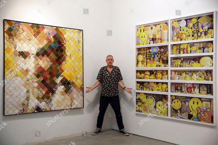 Fatboy Slim, aka Fat Boy Slim, poses for a photo at the Underdogs Gallery in Lisbon,. At left is a piece by Estudio Pedrita titled HarveyBall.jpg and at right a composite of photos showing Cook's collection of objects featuring the smiley face symbol. Smile High Club, an exhibition of art works that incorporate the smiley face and curated by Cook, opens Friday at the gallery