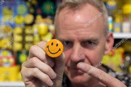 Fatboy Slim, aka Fat Boy Slim, shows a 1960's Smiley button from his collection of objects featuring the smiley face symbol at the Underdogs Gallery in Lisbon,. Smile High Club, an exhibition of art works that incorporate the smiley face and curated by Cook, opens Friday at the gallery