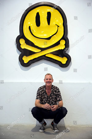 Fatboy Slim, aka Fat Boy Slim, poses underneath an art piece by RYCA titled Bonio 2019 original, at the Underdogs Gallery in Lisbon,. Smile High Club, an exhibition of art works that incorporate the smiley face and curated by Cook, opens Friday at the gallery