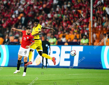 Abdallah Mahmoud Said Mohamed Bekhit of Egypt and Marshal Nyasha Munetsi of Zimbabwe challenging for the ball during the African Cup of Nations match between Egypt and Zimbabwe at the Cairo International Stadium in Cairo, Egypt