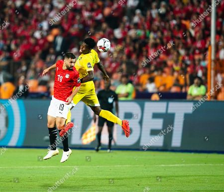 Stock Photo of Abdallah Mahmoud Said Mohamed Bekhit of Egypt and Marshal Nyasha Munetsi of Zimbabwe challenging for the ball during the African Cup of Nations match between Egypt and Zimbabwe at the Cairo International Stadium in Cairo, Egypt