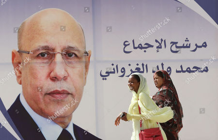 Women walk past an election poster of Mohamed Ould Cheikh Mohamed Ahmed Ghazouani, the ruling party's candidate, on a street of Nouakchott, Mauritania, 21 June 2019. Mauritania will vote on 22 June for the first round of a presidential election for a successor to President Mohamed Ould Abdel Aziz, who is stepping down after his second and final term in office.
