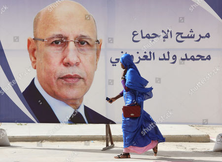 A woman walks past an election poster of Mohamed Ould Cheikh Mohamed Ahmed Ghazouani, the ruling party's candidate, on a street of Nouakchott, Mauritania, 21 June 2019. Mauritania will vote on 22 June for the first round of a presidential election for a successor to President Mohamed Ould Abdel Aziz, who is stepping down after his second and final term in office.