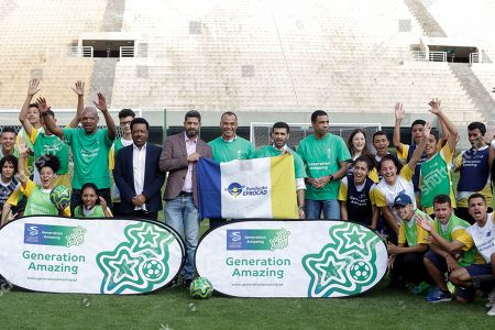 Former Brazilian soccer player Cafu, center, poses for pictures with Hassan Al Thawadi, center left, Chairman of the FIFA World Cup Qatar 2022, and Nasser Al-Khater, center right, deputy-secretary general of the Qatar 2022 organizing committee, and young soccer players, during a event where Cafu was presented as an Ambassador for the World Cup 2022, in Sao Paulo, Brazil