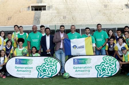 Former Brazilian soccer player Cafu, center, poses for pictures with Hassan Al Thawadi, center left, Chairman of the FIFA World Cup Qatar 2022, and Nasser Al-Khater, center right, deputy-secretary general of the Qatar 2022 organizing committee, and youth soccer players, during a event where Cafu was presented as an Ambassador for the World Cup 2022, in Sao Paulo, Brazil