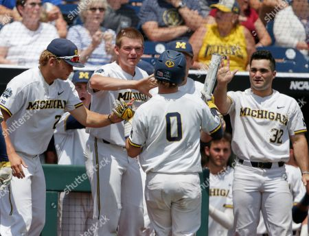 Michigan's Joe Donovan (0) is greeted at the dugout after he scored against Texas Tech when Jordan Brewer was hit by a pitch with the bases loaded, during the second inning of an NCAA College World Series baseball elimination game in Omaha, Neb., . Michigan won 15-3
