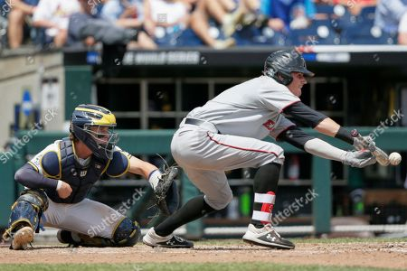Cody Masters, Joe Donovan. Texas Tech's Cody Masters hits a sacrifice bunt in front of Michigan catcher Joe Donovan during the third inning of an NCAA College World Series baseball elimination game in Omaha, Neb., . Michigan won 15-3