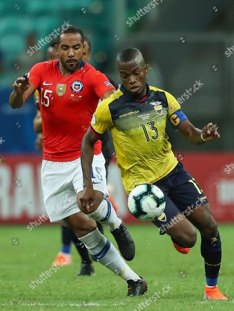 Ecuador's Enner Valencia, right, vies for the ball with Chile's Jean Beausejour during a Copa America Group C soccer match at the Arena Fonte Nova in Salvador, Brazil