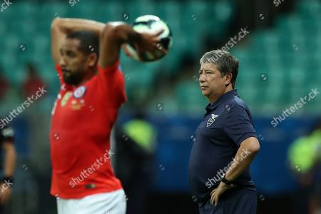 Ecuador's coach Hernan Gomez, right, watches from the sideline as Chile's Jean Beausejour throws the ball during a Copa America Group C soccer match at the Arena Fonte Nova in Salvador, Brazil