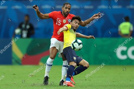 Ecuador's Angel Mena vies for the ball with Chile's Jean Beausejour during a Copa America Group C soccer match at the Arena Fonte Nova in Salvador, Brazil