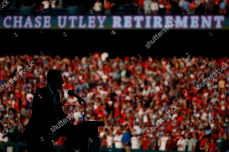 Former Philadelphia Phillies player Chase Utley is silhouetted during a retirement ceremony before a baseball game between the Phillies and the Miami Marlins, in Philadelphia