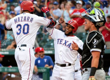 Texas Rangers' Nomar Mazara (30) is congratulated by Elvis Andrus, center, after hitting a two-run home run that scored Andrus off of Chicago White Sox starting pitcher Reynaldo Lopez during the first inning of a baseball game, in Arlington, Texas. White Sox catcher James McCann is at right