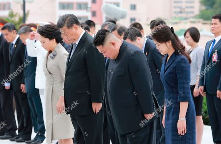 Provided by the North Korean government, North Korean leader Kim Jong Un, center right, his wife Ri Sol Ju, right, Chinese President Xi Jinping, center left, and his wife Peng Liyuan offer silent prayers as Xi laid a wreath at a memorial in Pyongyang, North Korea. The content of this image is as provided and cannot be independently verified
