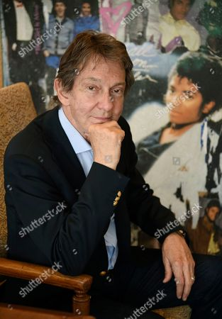 """Entertainment and corporate lawyer John Branca, the co-executor of Michael Jackson's estate, poses in his office next to an artwork presented to him from Sony Music commemorating the sale of 100 million copies of Michael Jackson's album """"Thriller,"""" at the law firm of Ziffren Brittenham LLP in Los Angeles"""