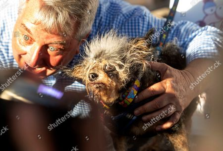 Stock Photo of Scamp the Tramp is held after taking top honors in the World's Ugliest Dog Contest at the Sonoma-Marin Fair in Petaluma, Calif., . At left is Kerry Sanders, a reporter who served as one of the judges
