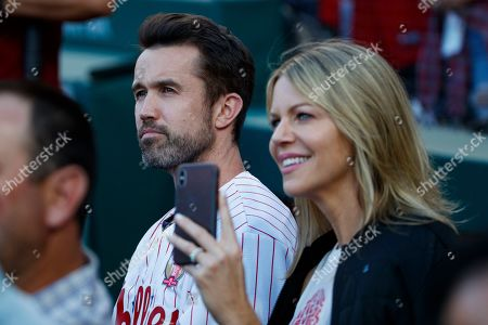 "Actor Rob McElhenney, left, creator of ""It's Always Sunny in Philadelphia"" sits with his wife, Kaitlin Olson, during a retirement ceremony for former Philadelphia Phillies' Chase Utley before a baseball game between the Philadelphia Phillies and the Miami Marlins, in Philadelphia"