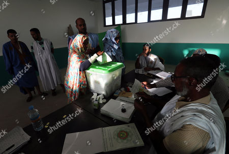 Stock Photo of A Mauritanian woman casts her ballot at a polling station during the Presidential election  in Nouakchott, Mauritania, 22 June 2019.  Mauritania votes on 22 June for the first round of a presidential election for a successor to President Mohamed Ould Abdel Aziz, who is stepping down after his second and final term in office.