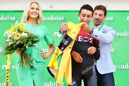 Stock Image of Colombian rider Egan Bernal (C) of Team Ineos reacts on the podium next to former Miss Switzerland Linda Faeh (L) and former Swiss rider Fabian Cancellara (R) after the eigth stage of the 83rd Tour de Suisse UCI ProTour cycling race, an individual time trial over 19.2km in Goms, Switzerland, 22 June 2019. Bernal retained the overall leader's yellow jersey.