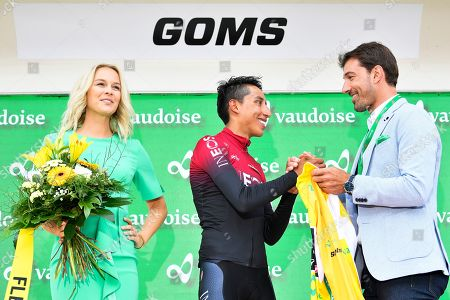 Stock Picture of Colombian rider Egan Bernal (C) of Team Ineos reacts on the podium next to former Miss Switzerland Linda Faeh (L) and former Swiss rider Fabian Cancellara (R) after the eigth stage of the 83rd Tour de Suisse UCI ProTour cycling race, an individual time trial over 19.2km in Goms, Switzerland, 22 June 2019. Bernal retained the overall leader's yellow jersey.