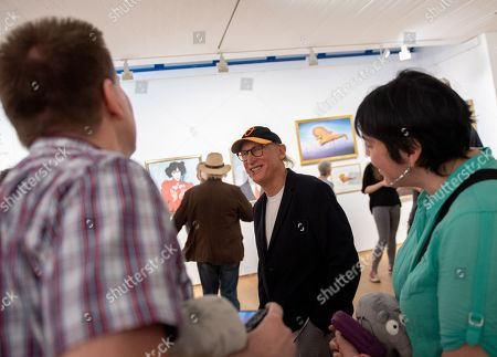 German comedian Otto Waalkes (C) talks to visitors about some of his paintings at the Kunsthalle Emden, in Emden, northern Germany, 22 June 2019. The museum is presenting an exhibition of artworks by Otto, who was born in Emden, from 22 June to 22 September 2019.