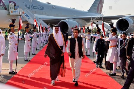 In this photo released by Press Information Department, Emir of Qatar Sheikh Tamim bin Hamad Al Thani, center left, walks with Pakistani Prime Minister Imran Khan upon his arrival at Nur Khan airbase in Rawalpindi, Pakistan, . Emir of Qatar Sheikh Tamim bin Hamad Al Thani arrived Islamabad on a two-day visit to discuss bilateral, international and regional issues with Pakistani leadership