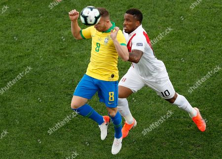 Brazil's Arthur, left, and Peru's Jefferson Farfan, compete for the ball during a Copa America Group A soccer match at the Arena Corinthians in Sao Paulo, Brazil