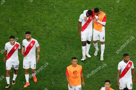 Stock Picture of Peru's Miguel Araujo (5) and Anderson Santamaria (4) leave the field embraced after their 0-5 lost against Brazil during a Copa America Group A soccer match at the Arena Corinthians in Sao Paulo, Brazil