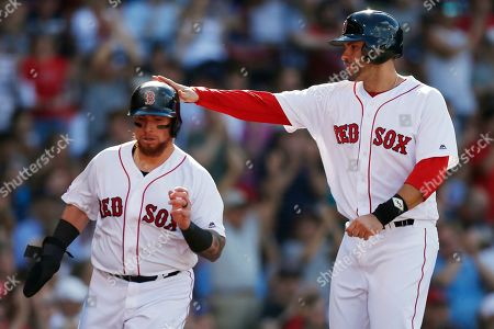 Boston Red Sox's J.D. Martinez, right, and Christian Vazquez celebrate after scoring on a double by Jackie Bradley Jr. during the second inning of a baseball game against the Toronto Blue Jays in Boston