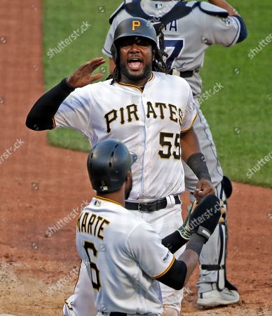 Pittsburgh Pirates' Josh Bell (55) celebrates with Starling Marte (6) after the two scored on an RBI single by Adam Frazier off San Diego Padres relief pitcher Craig Stammen during the eighth inning of the team's baseball game in Pittsburgh, . The Pirates won 6-3