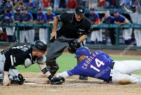 Ed Hickox, Asdrubal Cabrera, Zack Collins. Chicago White Sox catcher Zack Collins, left, reaches to tag out Texas Rangers' Asdrubal Cabrera (14) as umpire Ed Hickox looks on in the first inning of a baseball game in Arlington, Texas, . Cabrera was trying to score on a double by Logan Forsythe