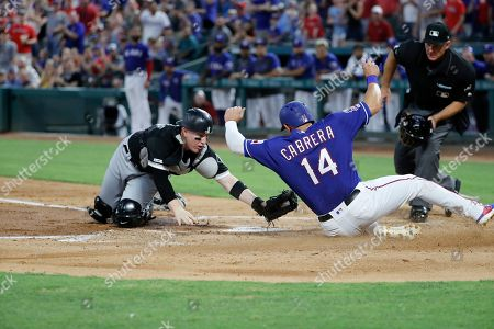 Ed Hickox, Asdrubal Cabrera, Zack Collins. Chicago White Sox catcher Zack Collins (38) reaches down to tag out Texas Rangers' Asdrubal Cabrera (14) as upire Ed Hickox looks on in the first inning of a baseball game in Arlington, Texas, . Cabrera was trying to score on a double by Logan Forsythe