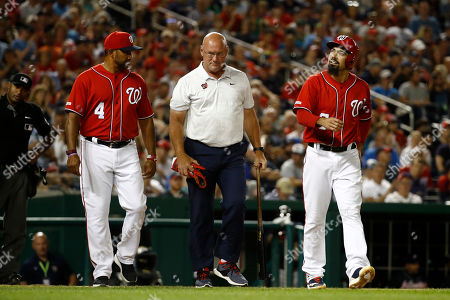 Stock Photo of Washington Nationals' Anthony Rendon, right, walks to first alongside manager Dave Martinez, left, and head athletic trainer Paul Lessard after getting hit by a pitch in the seventh inning of a baseball game against the Atlanta Braves, in Washington